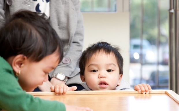 Toddler peering over the edge of a small table, while her twin is climbing onto the table in the foreground