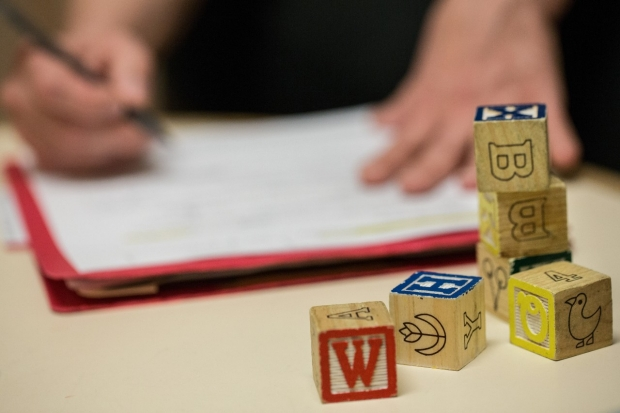 Wooden blocks with letters, numbers and pictures stacked in front of a folder that someone is writing on