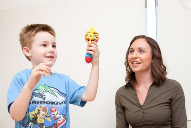 Dr. Casey Krueger and little boy holding up a noise making toy