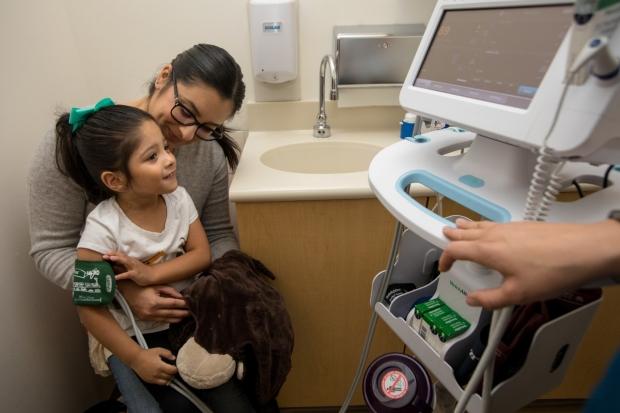 A child has her blood pressure taken.