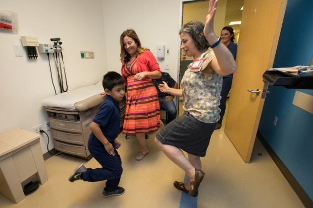 A child stands on one foot, as demonstrated by Drs. Tina Buysse and Sarah Dubner.