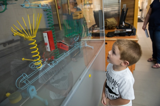 A child follows the path of a ball in the Rube Goldberg machine [a complex machine to accomplish simple tasks] in the lobby at 730 Welch Road in Palo Alto.