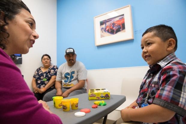 Dr. Julie Youssef asks questions of a little boy.
