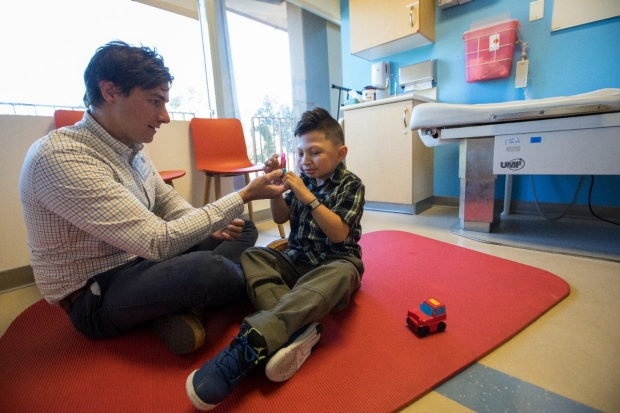 Psychologist Dr. Mark Beidelman sits on a mat to evaluate a child.