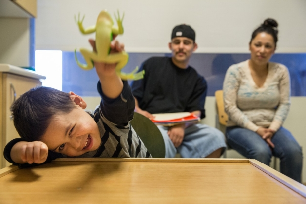 A patient plays with a toy frog as his parents look on.