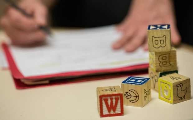 Wooden blocks with letters, numbers and pictures on the side, stacked in front of a folder that someone is writing on