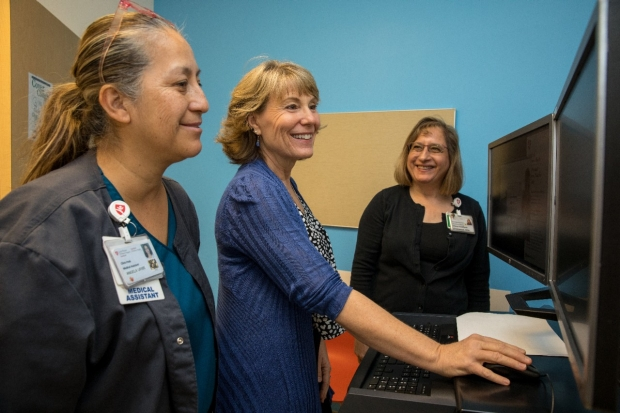 Angela Uribe, Sandy Lombardi-Lytle and Cheryl Goldfarb-Greenwood look at a computer screen to record patient information.